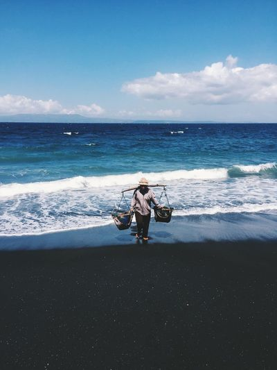 Full Length Of Vendor With Baskets At Beach Against Sky