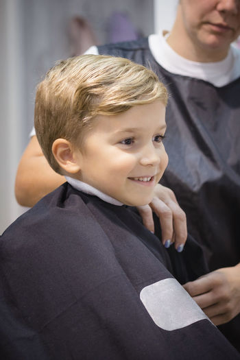 Smiling boy sitting at barber shop