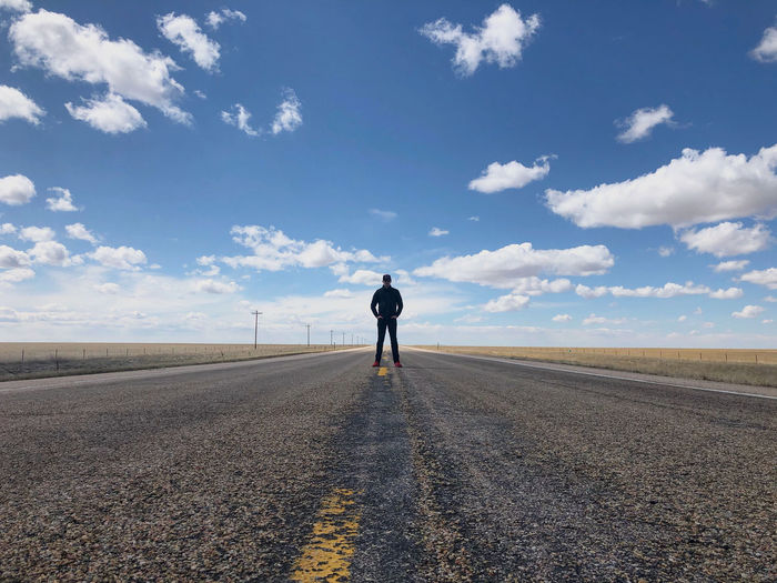 Front view of man standing on road against sky