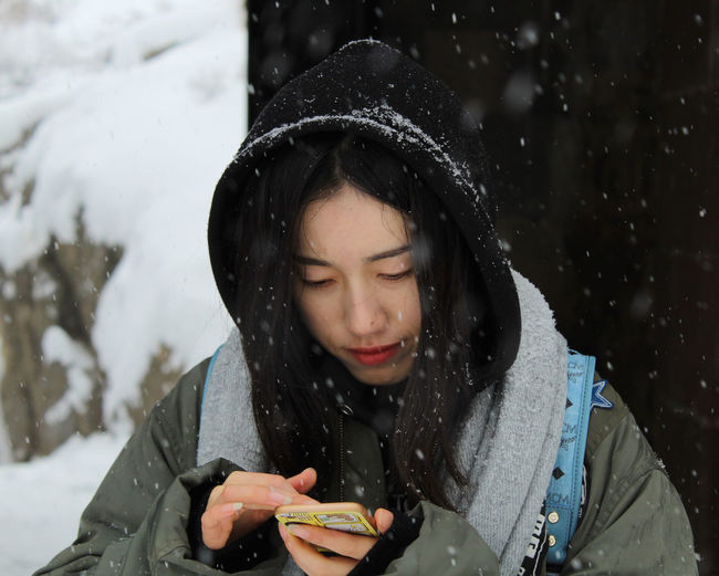 Close-up of young woman using phone during snowfall
