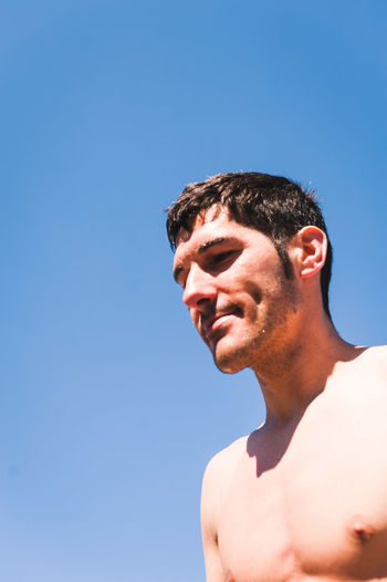 Portrait of shirtless man against clear blue sky