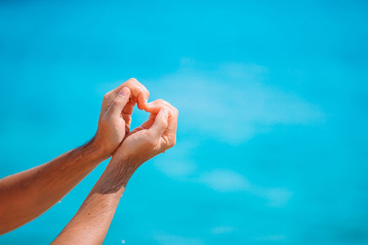 Cropped hands of man making heart shape against sea
