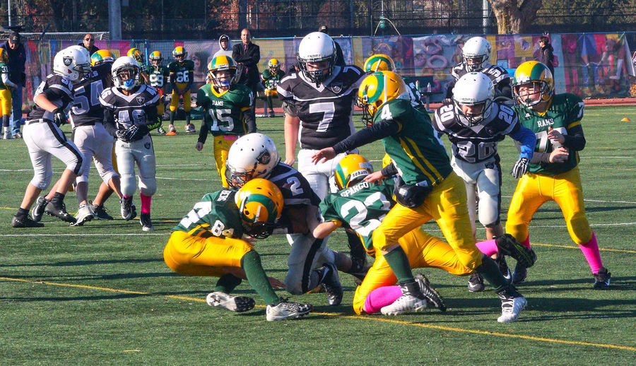 Junior football at Minoru Park in Richmond B.C. Canada. Multi Colored Day Outdoors Real People Competition Headwear Sportsman Challenge Team Sport Junior Football Canada B.C Richmond Playing Field Sports Uniform Teamwork Sports Team Athlete Competitive Sport Sports Helmet
