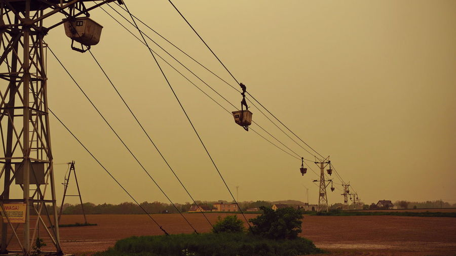 Low angle view of overhead cable cars against clear sky