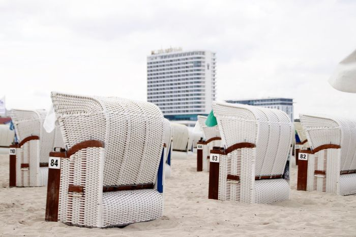 EyeEm Selects Beach Sand Hooded Beach Chair Sea Day Whicker Chair Outdoors Sky Building Exterior Architecture Vacations No People Nature