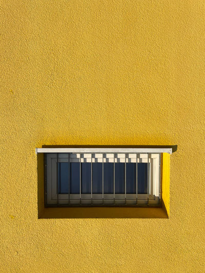 Close-up of yellow window on wall