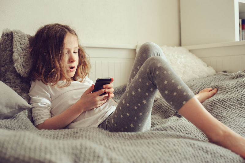 kid girl playing smartphone at home on the bed Indoors  Communication Lifestyles Wireless Technology Technology Portable Information Device Smart Phone Playing Childhood Child Girl Kid Preschooler Bed Nursery Authentic Moments Relaxing Cute Funny Learning Home