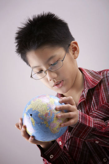 Boy holding globe against white background