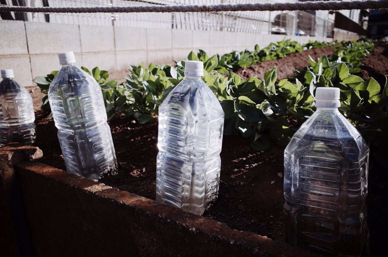Close-Up Of Water Bottles On Field Against Fence