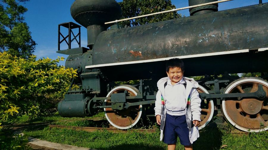 Boy Standing By Steam Train On Sunny Day