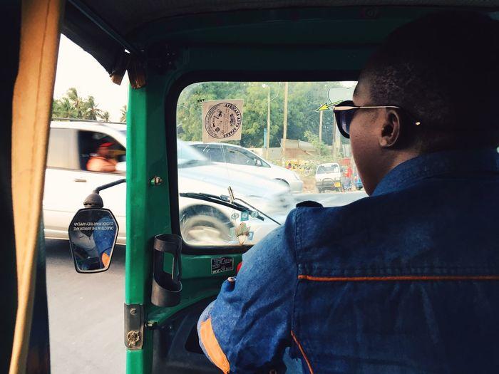Rear view of man driving rickshaw on street