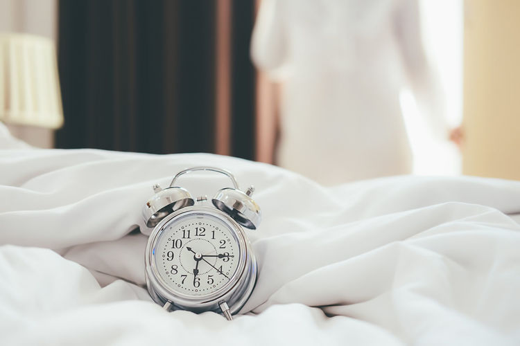 Alarm Clock Bed Bedroom Clock Close-up Domestic Room Focus On Foreground Furniture Indoors  Lifestyles Linen Midsection One Person Real People Relaxation Sleeping Textile Time White Color