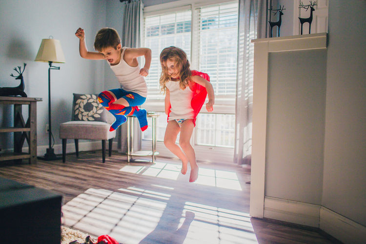 Child Day Family Home Interior Indoors  Jumping Lifestyles Living Room Playing Siblings Smiling Super Hero Two People