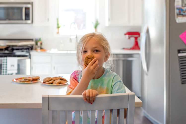 Portrait of cute girl eating cookie at home
