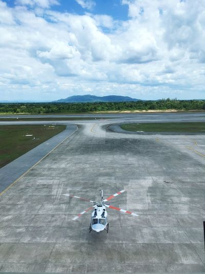 High Angle View Of Helicopter At Airport Runway Against Cloudy Sky