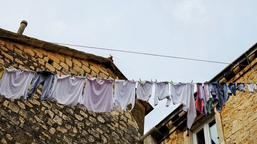 Drying clothes Drying Hanging Clothesline Laundry Building Exterior Clothing Built Structure Architecture Clothespin Low Angle View Outdoors No People Day Residential Building Cloth Sky