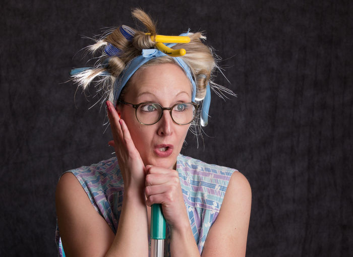 Woman wearing hair curlers against wall
