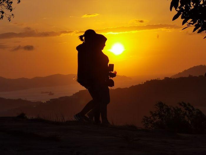 Silhouette man standing against orange sky