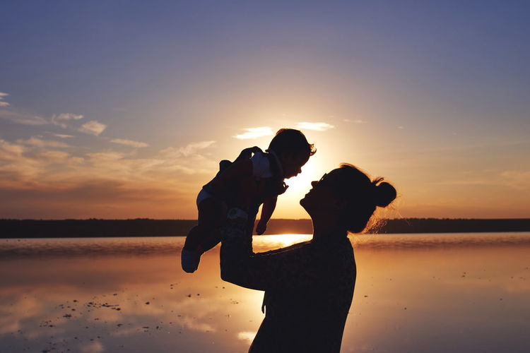 Woman with a child silhouette at the sunset time by the sea