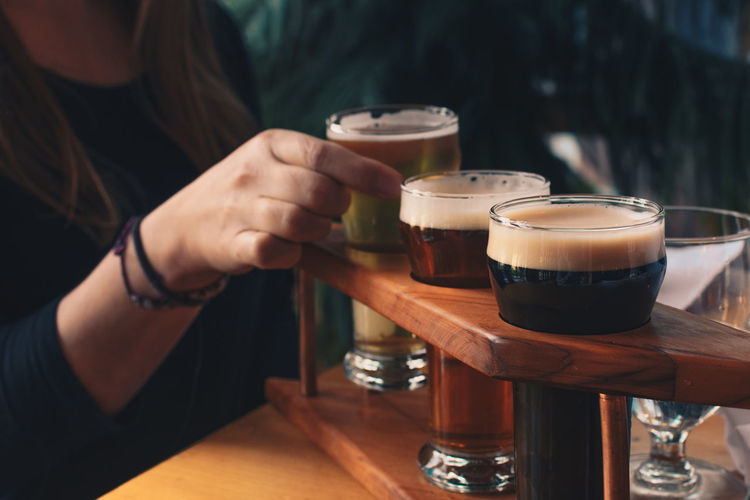 Cropped image of woman tasting craft beer at bar