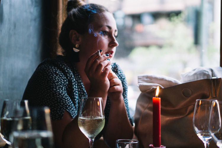 Side view of woman smoking cigarette while sitting with wineglass at restaurant table