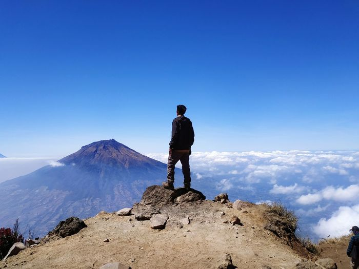 Back view of man alone standing on mountain looking up at blue blue sky