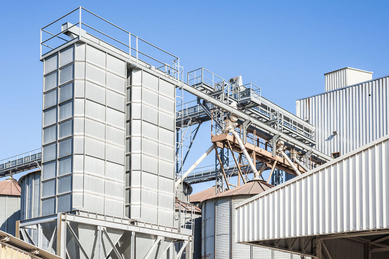 Storage facility cereals and production of bio gas; silos and drying towers Agricultural Blue Building Exterior Cereals Clear Sky Container Day Factory Food Industry Iron - Metal Outdoors Silos Sky Storage Tall - High Tanks Tower