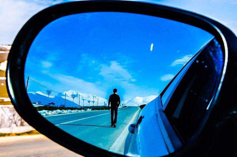 Rear view of man on road reflecting in car side-view mirror