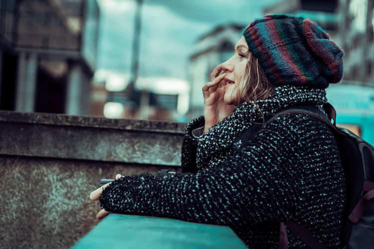 Woman in warm clothing standing by retaining wall in city