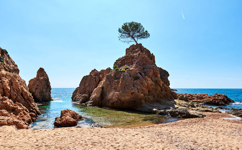 Rock formations on shore at beach in tossa de mar