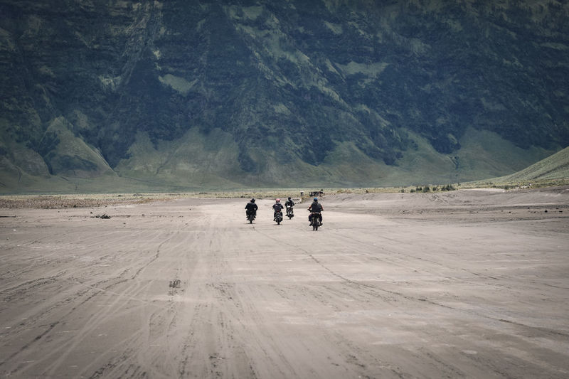 Rear view of people riding motorcycles on mountain road