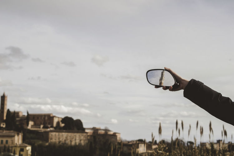 Cropped image of hand holding mirror with reflection of torre del mangia