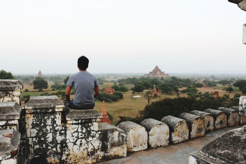 Rear view of man sitting on retaining wall at temple while looking at landscape against sky