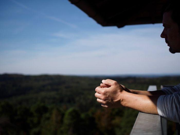 Man leaning on railing of balcony