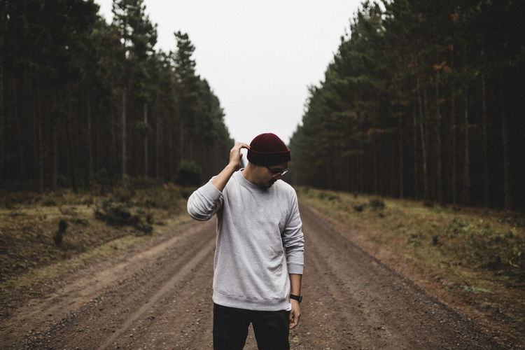 Young man touching knit hat while standing on dirt road amidst trees