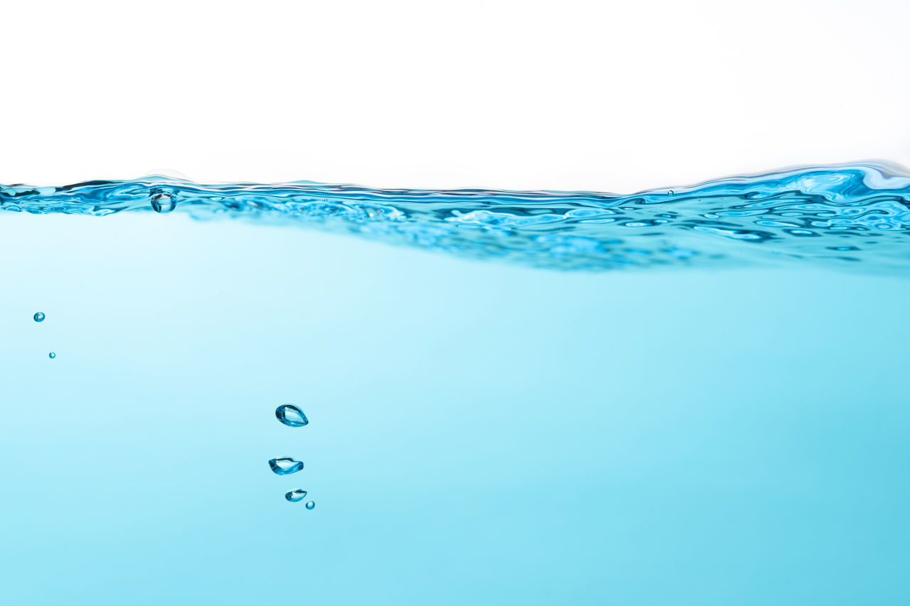 CLOSE-UP OF WATER DROPS OVER BLUE BACKGROUND
