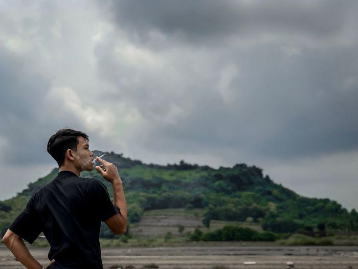 Man smoking cigarette against cloudy sky