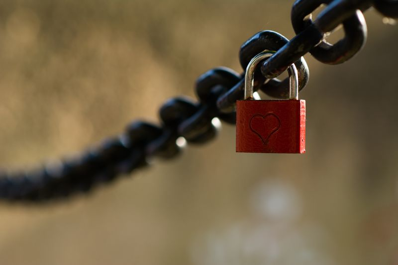 Close-Up Of Heart Shape On Padlock Hanging On Metal Chain