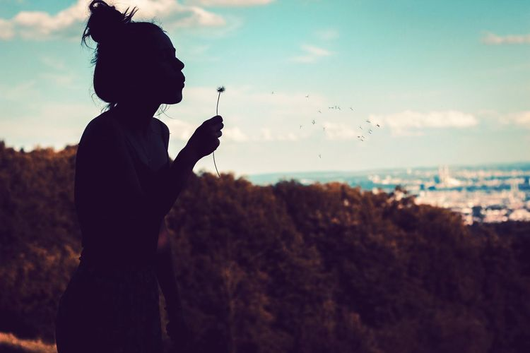 Side View Of Silhouette Woman Blowing Dandelion Against Sky
