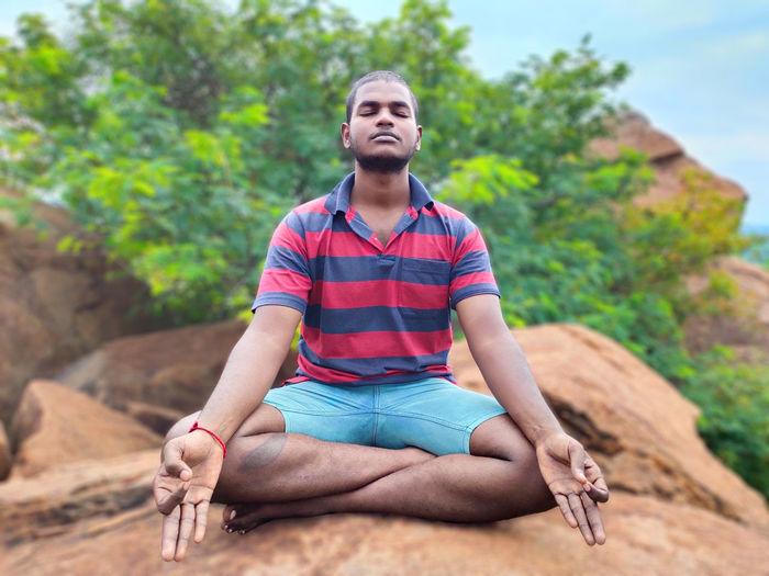 Young man doing yoga on rock