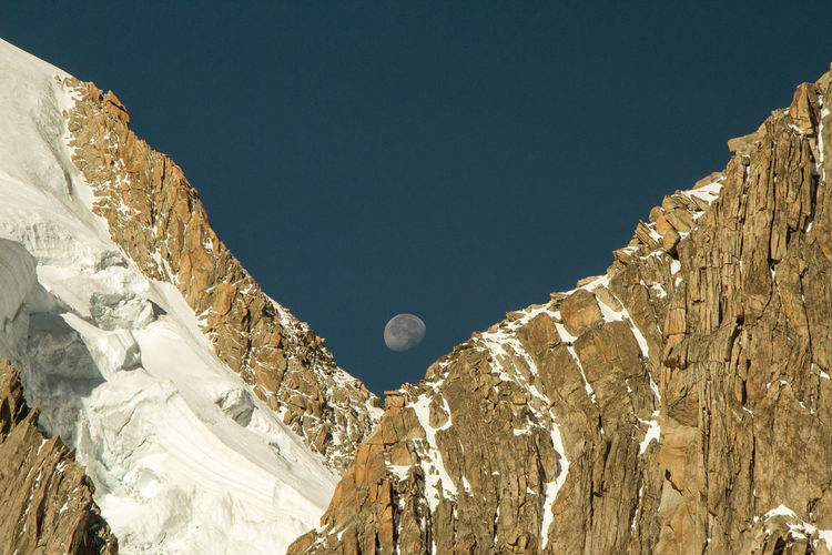 Idyllic shot of moon over rocky mountains against clear sky