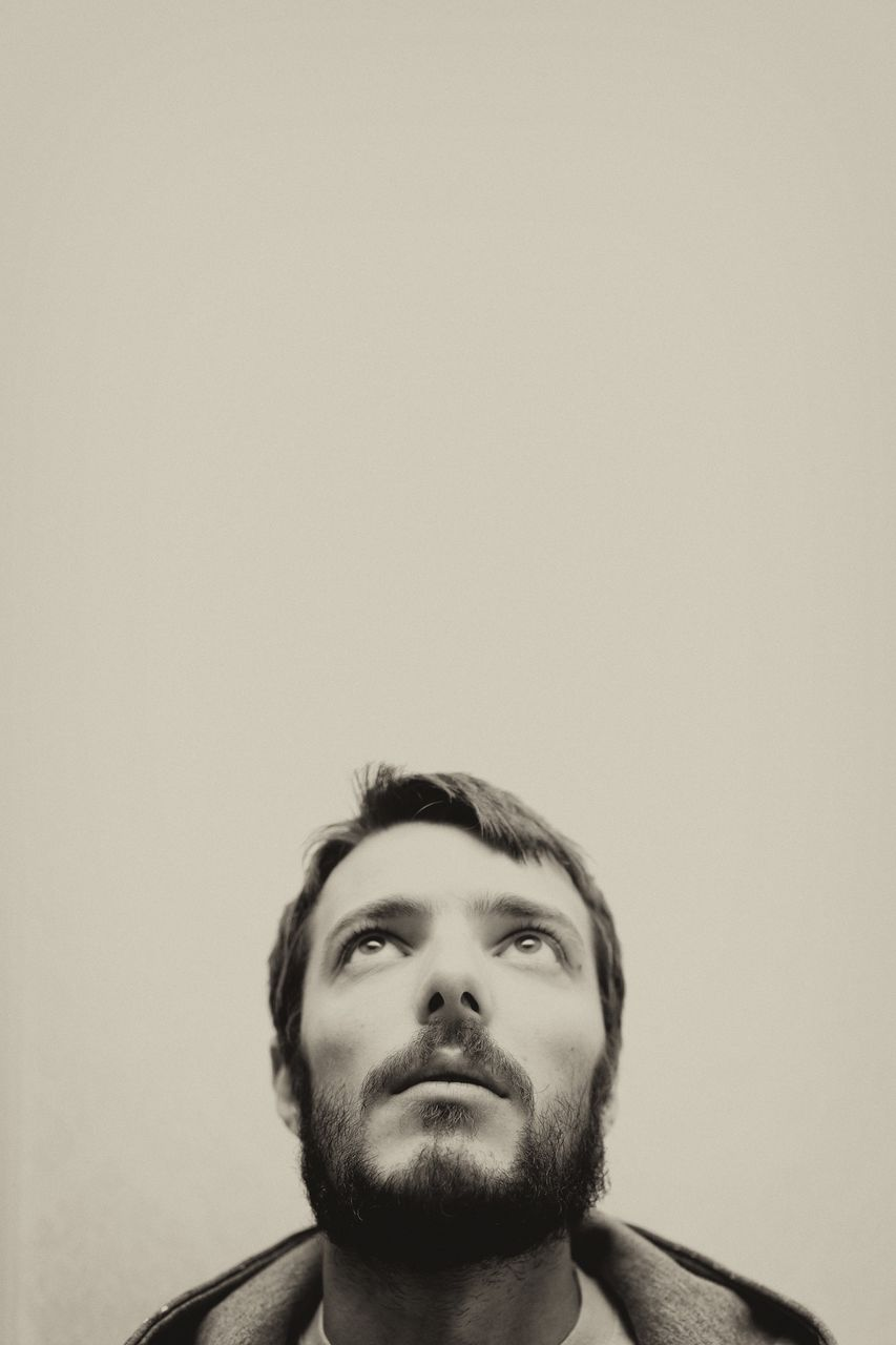Headshot Of Man Looking Up Against Wall