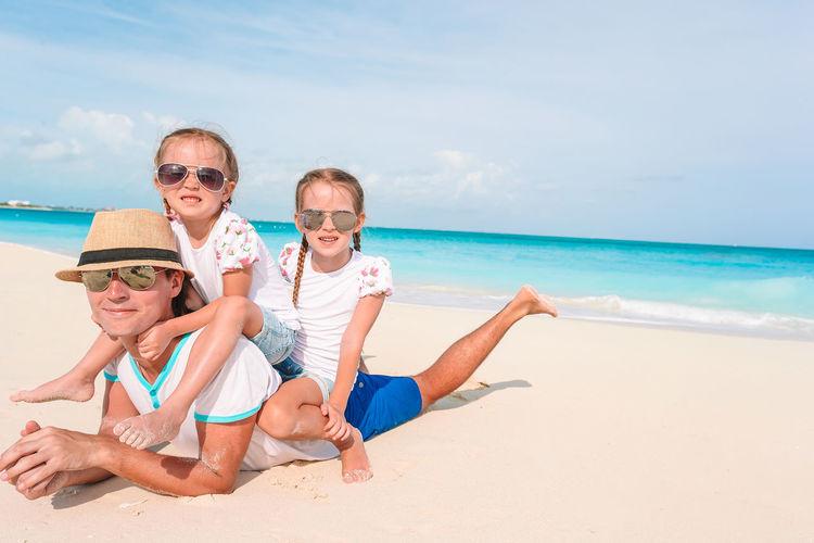 Full length of friends on beach against sea against sky