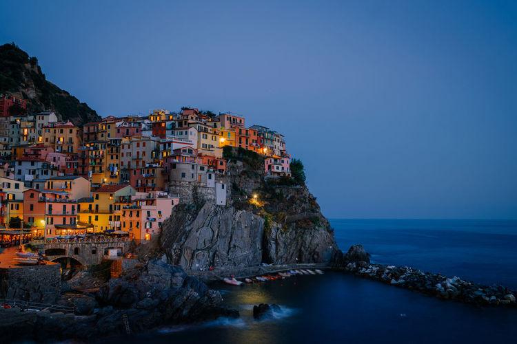 Illuminated city by sea against clear sky at dusk