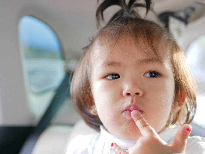 Little Asian baby girl putting her finger on her lips thinking of something Travel Trip Car Inside Little Asian  Baby Girl Cute Adorable Finger Touch Point Lips Thinking Pondering Child Kid Toddler  Young Childhood Headshot One Person Babyhood Put