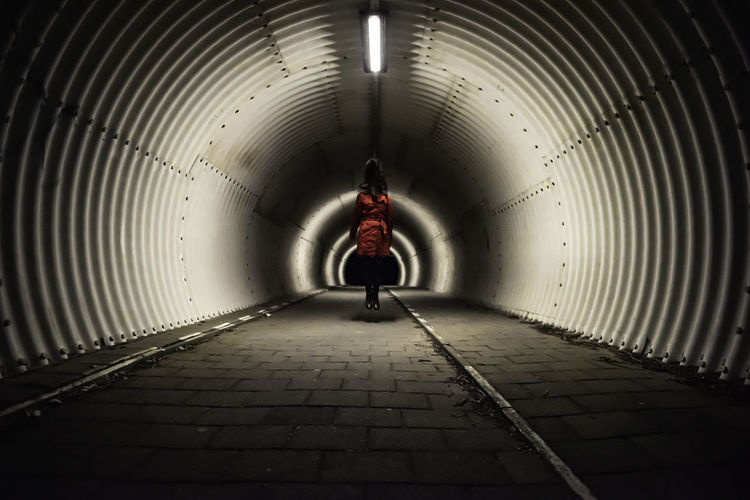 Rear view of man walking in illuminated tunnel