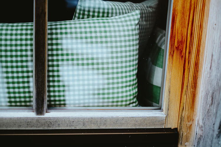 Close-up of pillow behind window