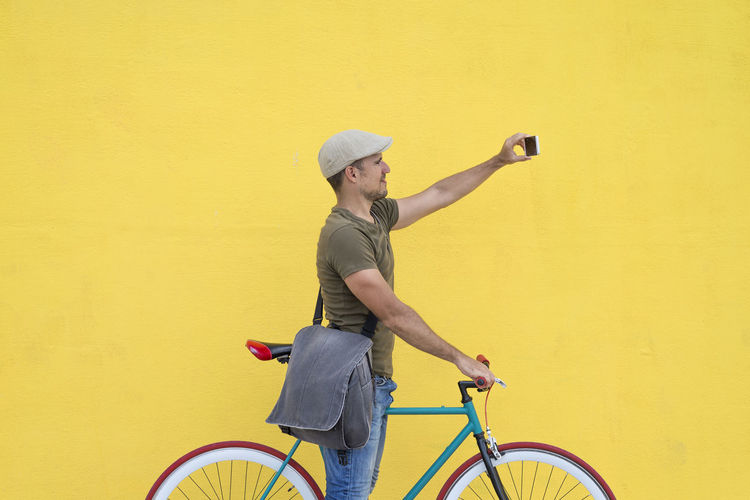 Man taking selfie while standing with bicycle against yellow wall