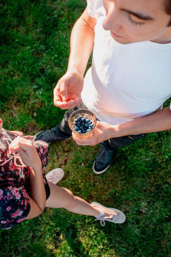Teenager girl and boy enjoying eating the fresh blueberries outdoors standing in a garden in the summer. Girl wearing red-blue flowery blouse, boy wearing white t-shirt. Boy holding glass filled with freshly picked berries. Shot from above Berries Dessert Eating Freshness Life Woman Young Berry Blueberries Blueberry Enjoying Enjoyment Female Food Fresh Fruit Garden Girl Healthy Joy Organic Outdoors person Summer Sweet
