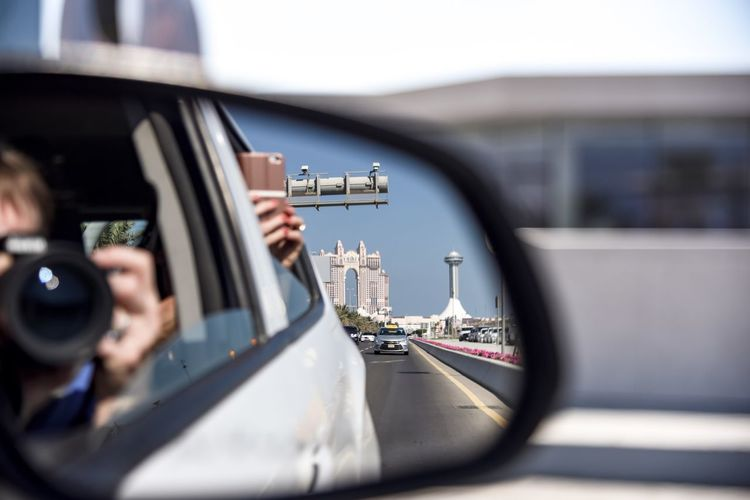 On a journey through abu dhabi -drive by car and take pictures through the open windowpane